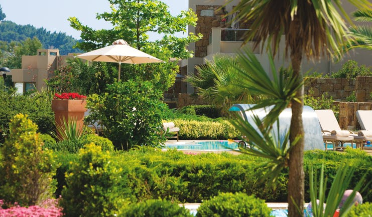 Sani Asterias Greece gardens next to outdoor pool with lounger