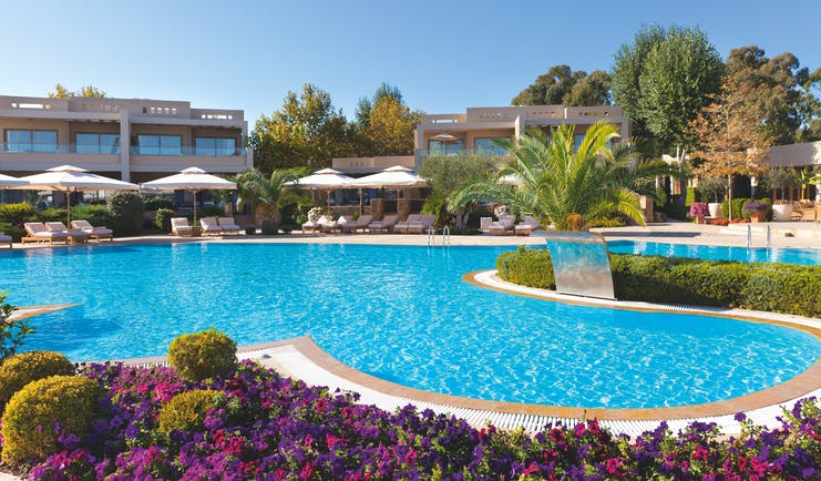 Sani Asterias Greece outdoor swimming pool next to pink and purple flowers with loungers and umbrellas