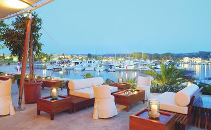 Sani Asterias Greece terrace bar outdoor lounge area with sofas next to boats docked in marina