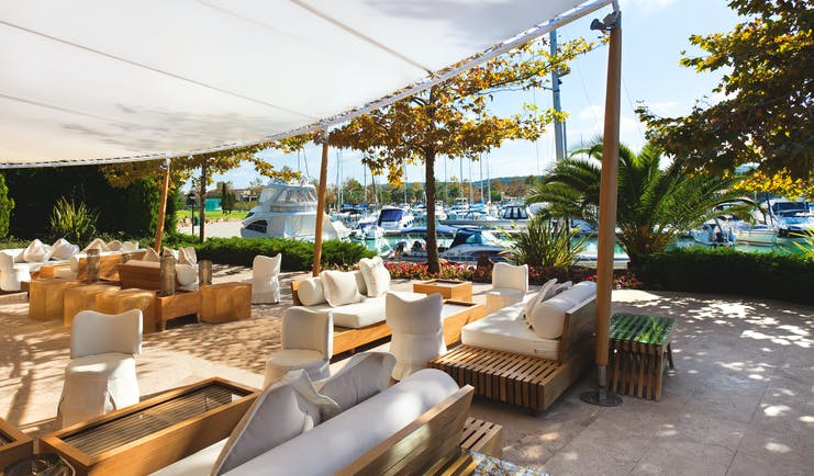 Sani Asterias Greece terrace outdoor lounge area with sofas next to boats docked in marina