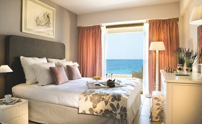 View of a Sani Beach family bedroom including a double bed and a large window a sea view