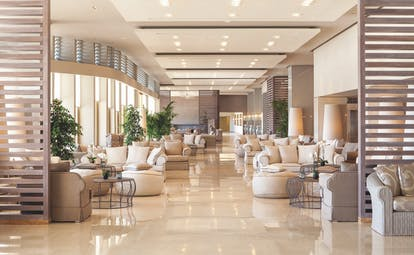 View of the Sani Beach lobby, comprising a big room with a cream and lilac colour scheme and arm chairs