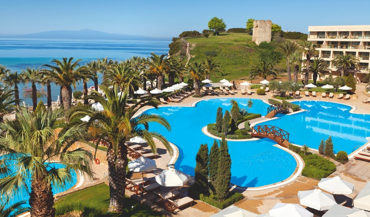Overview of the main pool at the Sani Beach with palm trees surrounding the blue pool