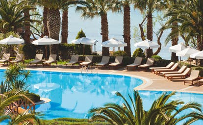 View of the pool at the Sani Beach with palm trees, umbrellas and deckchairs around the pool