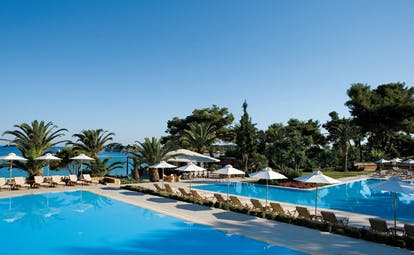 Sani Club Greece outdoor pool loungers umbrellas palm trees sea view