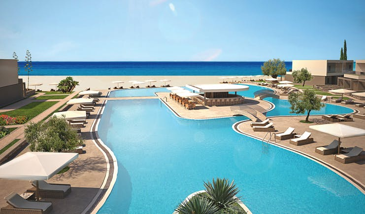 Overview of the pool at Sani Dunes with sunbeds and umbrellas surrounding the pool and leading onto the beach