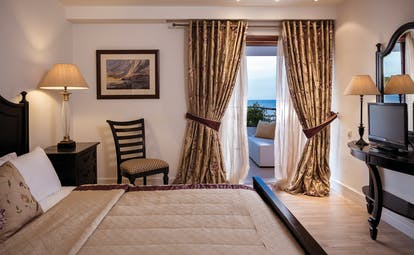 Bedroom at the Skiathos Princess Hotel in greece with large double bed, beige colour scheme and balcony with sea view