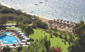 Overview of the Skiathos Princess hotel showing a large pool surrounded by white umbrellas and deck chairs. The beach is shown in close proximity