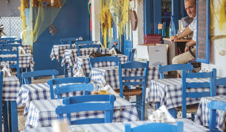 Restaurant seating area at the Skiathos Princess Hotel with blue painted wooden chairs and gingham table cloths covering the tables