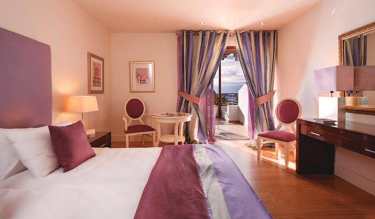 Suite at the Skiathos Princess Hotel  in Greece with large double bed, television, purple colour scheme and balcony with sea view