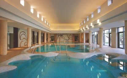 The Romanos Greece indoor pool with large windows