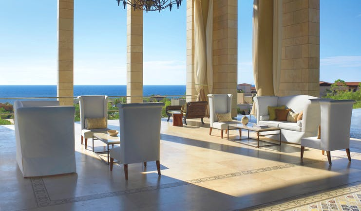 The Romanos Greece outdoor lobby with chairs and sofas