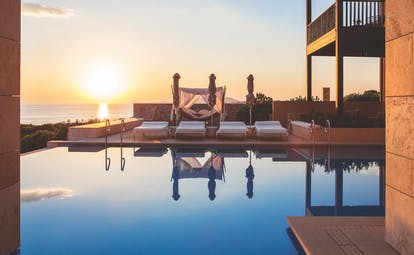 The Romanos Greece outdoor pool sunest with loungers and a hammock