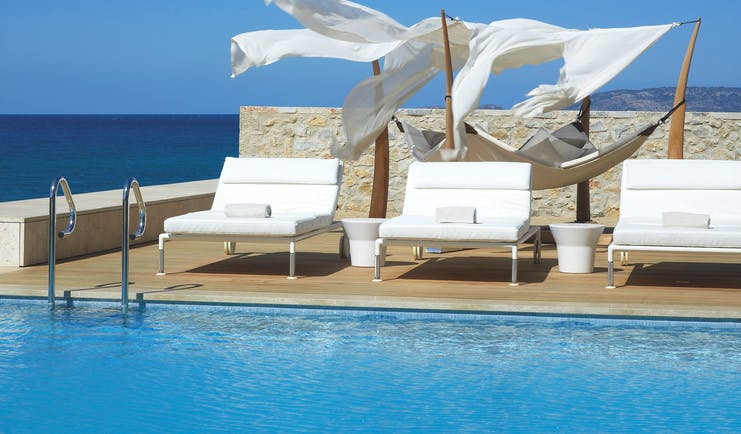 The Romanos Greece outside swimming pool with decked area with loungers and a hammock and sea view