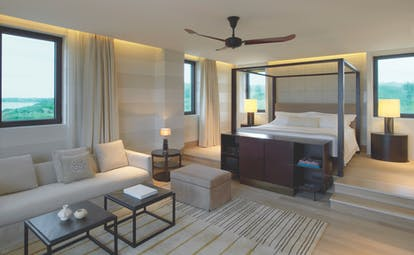 The Romanos Greece suite with sofa and raised sleeping area with large windows