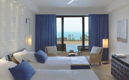 The Romanos Greece twin bedroom with blue curtains and patio doors to terrace
