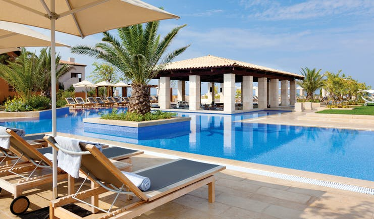 The Romanos Greece outdoor swimming pool with sun loungers and umbrellas
