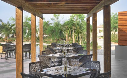 Outside dining area at the Westin Resort with black tables and chairs set out under a wooden roof