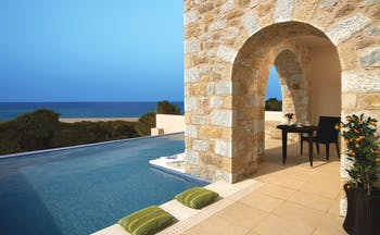 View of an outdoor infinity pool with green cushions on the pool edge and a stone arch walk-way