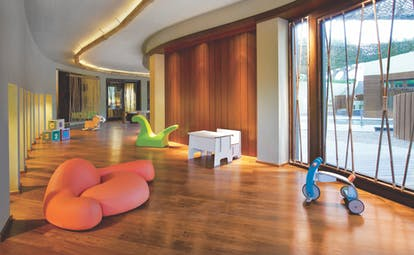 View of the kids club at the Westin Resort with curvy walls, wooden floors and toys scattered around the floor