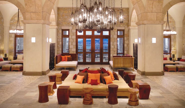 View of the Westin Resort lobby with big stone archways, pillars, a large, low hanging chandelier and cushioned seats