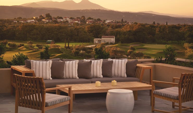 Outdoor lounge area at the Westin Resort with a benched seating area looking over to a mountain range covered by a yellow sunset