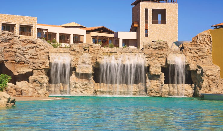 View of the outdoor pool with four waterfalls built into the rocks behind the pool