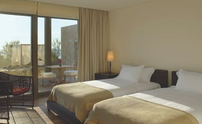 View of a twin room at the Westin Resort with two beds and a large window with doors opening onto a balcony
