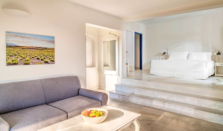 Vedema Resort Greece Aegean suite with lounge area sofa and steps leading to bed