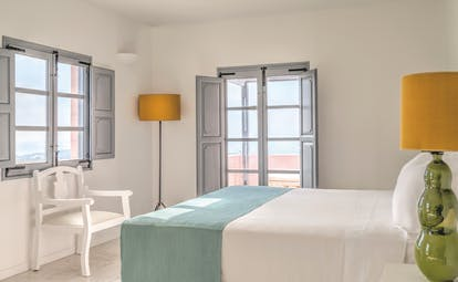 Vedema Resort Greece Dorian suite bedroom with window and grey shutters and patio doors