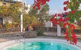 Vedema Resort Greece jacuzzi area with trees and red flowers