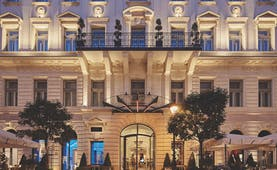 Aria Hotel Budapest exterior facade large cream stone building with a balcony and a ground floor terrace area