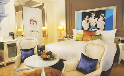Aria Hotel Budapest luxury bedroom cartoon portrait of Elvis Presley large mirror and two blue and white chairs