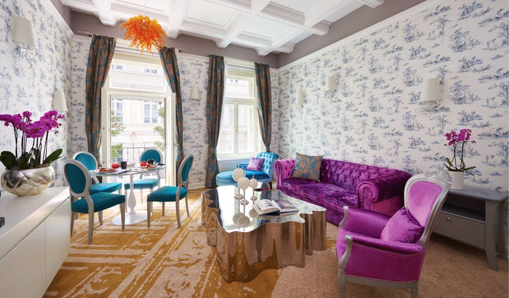 Aria Hotel Budapest suite sitting room  orange chandelier purple sofa and chair blue chaise longue table and blue chairs