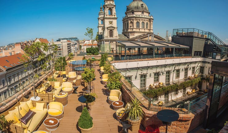 Aria Hotel Budapest rooftop terrace with yellow and brown chairs pot plants and view over a courtyard and cathedral
