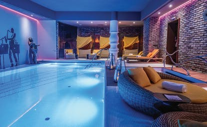 Aria Hotel Budapest indoor pool a mural of a jazz player a round sofa and yellow cabanas