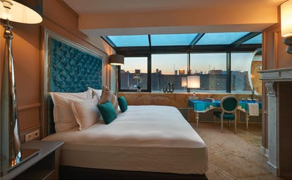 Aria Hotel Budapest suroom bed and blue desk chair and fireplace