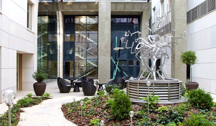 Continental Hotel courtyard garden, outdoor seating, flower beds, metal sculpture