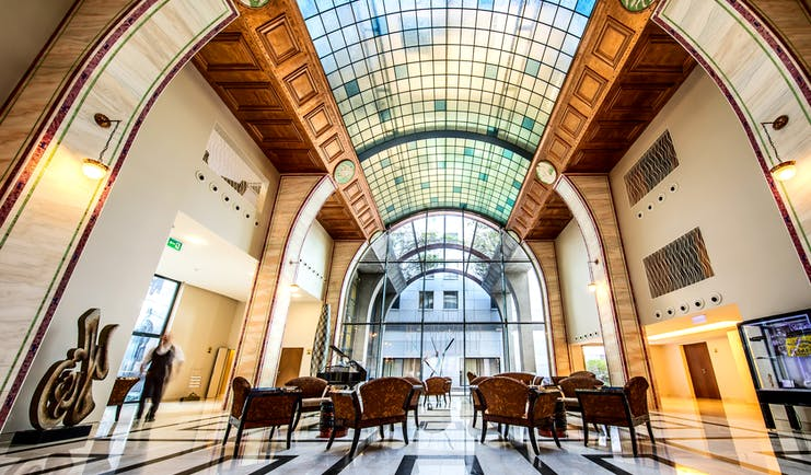 Continental Hotel lobby, art deco decor and architecture, glass arch shaped ceiling, marble floors, tables and chairs