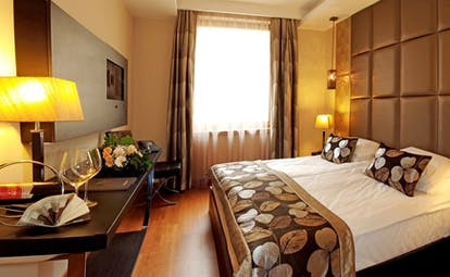 Continental Hotel standard room, double bed, desk, warm modern interiors