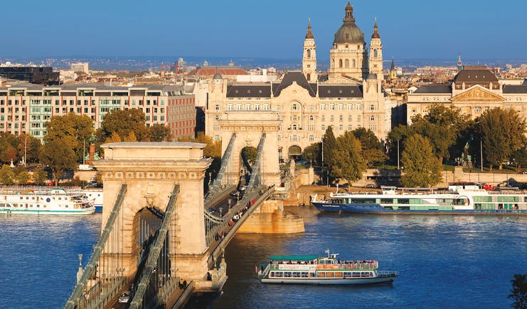A bridge with square towers either end across the blue Danube in Budapest