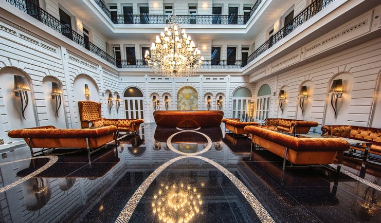 Prestige Hotel Budapest lobby lounge area black marble floor orange sofas and a chandelier