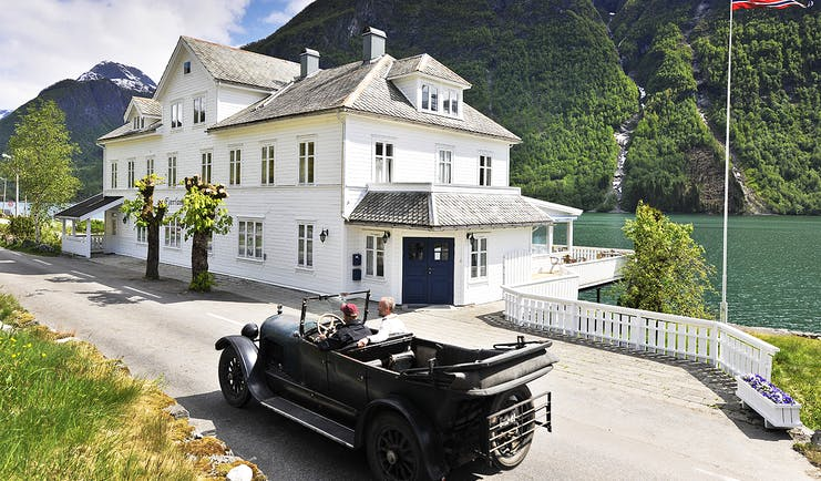 Fjaerland Fjordstove Hotell white hotel building on lake with vintage car in foreground