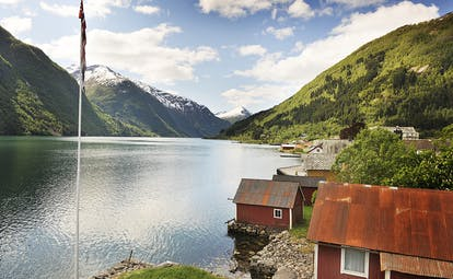 Fjaerland Fjordstove Hotell lake with flagpole and small cabins with red roofs by side