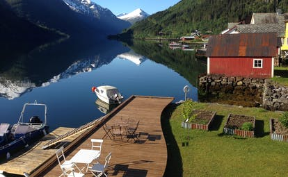 Fjaerland Fjordstove Hotell view of lake with snowy mountains and lakeside jetty with boat