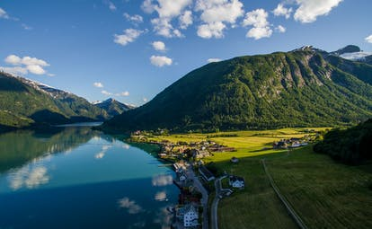 Fjaerland Fjordstove Hotell lake with green fields at side and wooden hills and mountains in distance