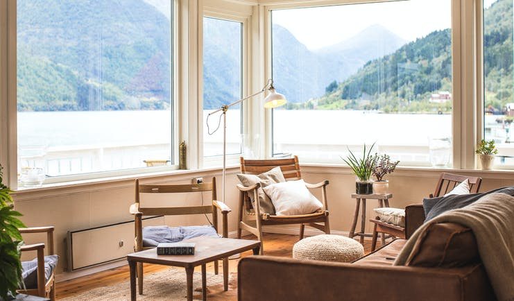 Fjaerland Fjordstove Hotell corner of room with large windows overlooking late with chairs and plants