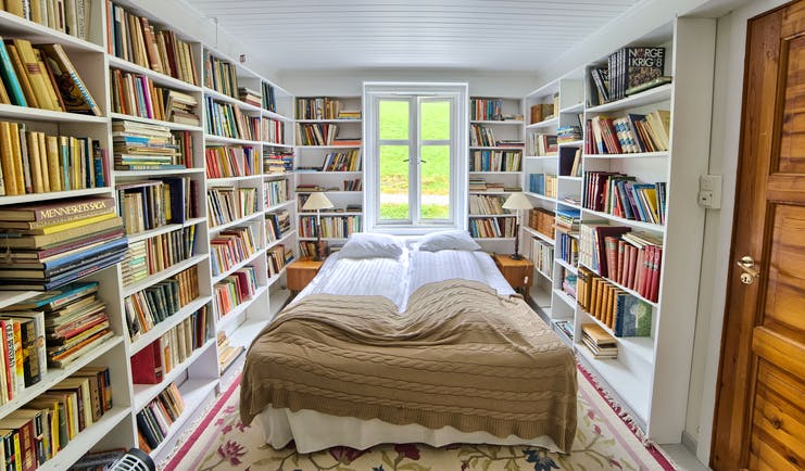 Fjaerland Fjordstove Hotell bedroom in room lined with books on white shelves