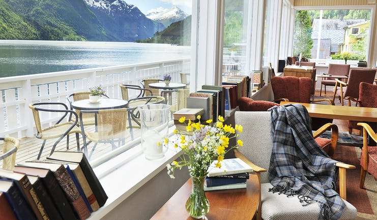 Fjaerland Fjordstove Hotell terrace with dining overlooking lake