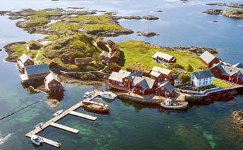Aerial view of island with jetty, boats and cabins